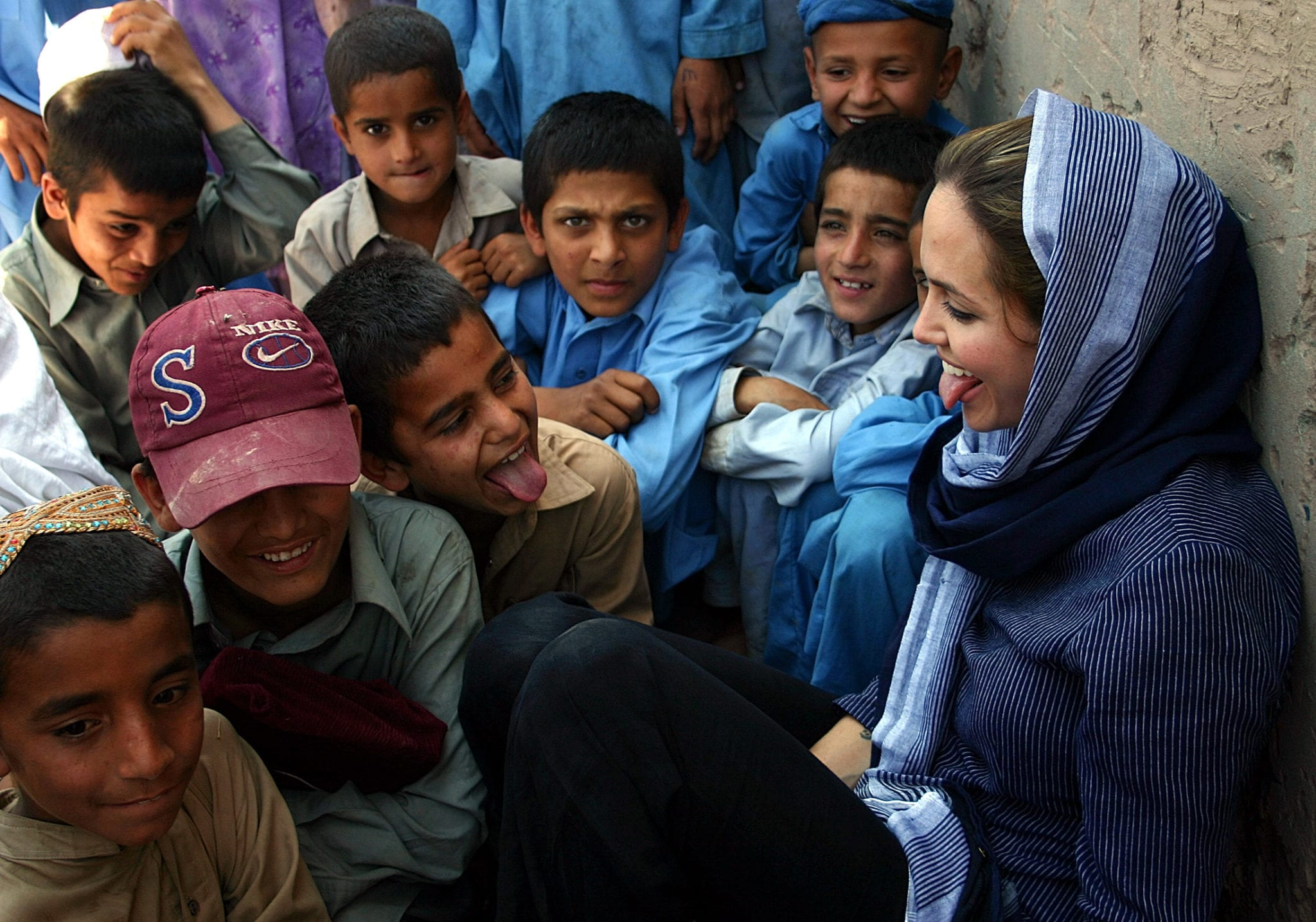 Hollywood actress and Oscar winner, Angelina Jolie (R), who is also the United Nations High Commissioner for Refugees (UNHCR) Goodwill Ambassador, plays with Afghan refugee children during her visit at Kacha Gari refugee camp in Peshawar May 5, 2005. Jolie asked on Saturday for increased international help to repatriate more than 3 million Afghans living in Pakistan. Picture taken May 5, 2005. REUTERS/UNHCR/Handout PAKISTAN REFUGEES JOLIE